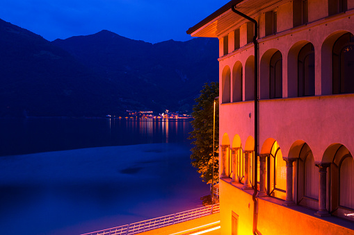 Night romantic Italian city of Lovere: a building with arches illuminated and a view of the lake