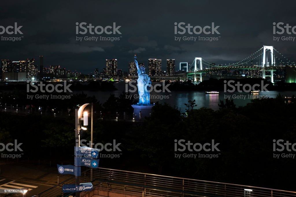Night scape of the replica statue of liberty and the rainbow bridge in Odaiba, Tokyo, Japan. stock photo