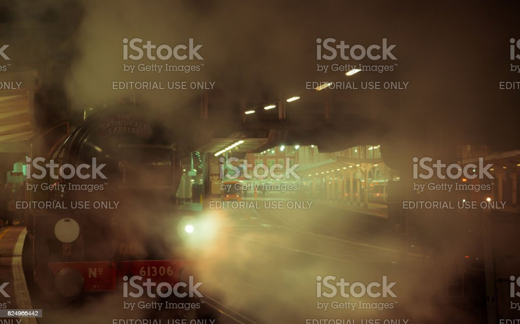 Night scene of a steam train pulling off at Victoria station in London stock photo