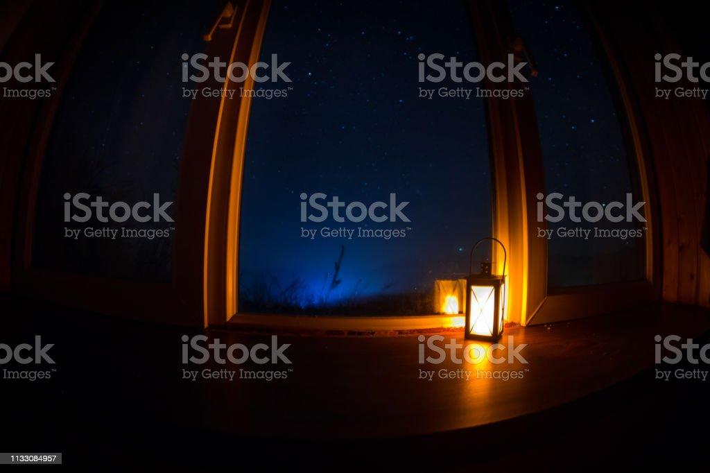 Night scene of stars seen through the window from dark room. Night...