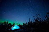 istock Night scene with illuminated camping tent, forest, starry sky and northern lights 1172261895