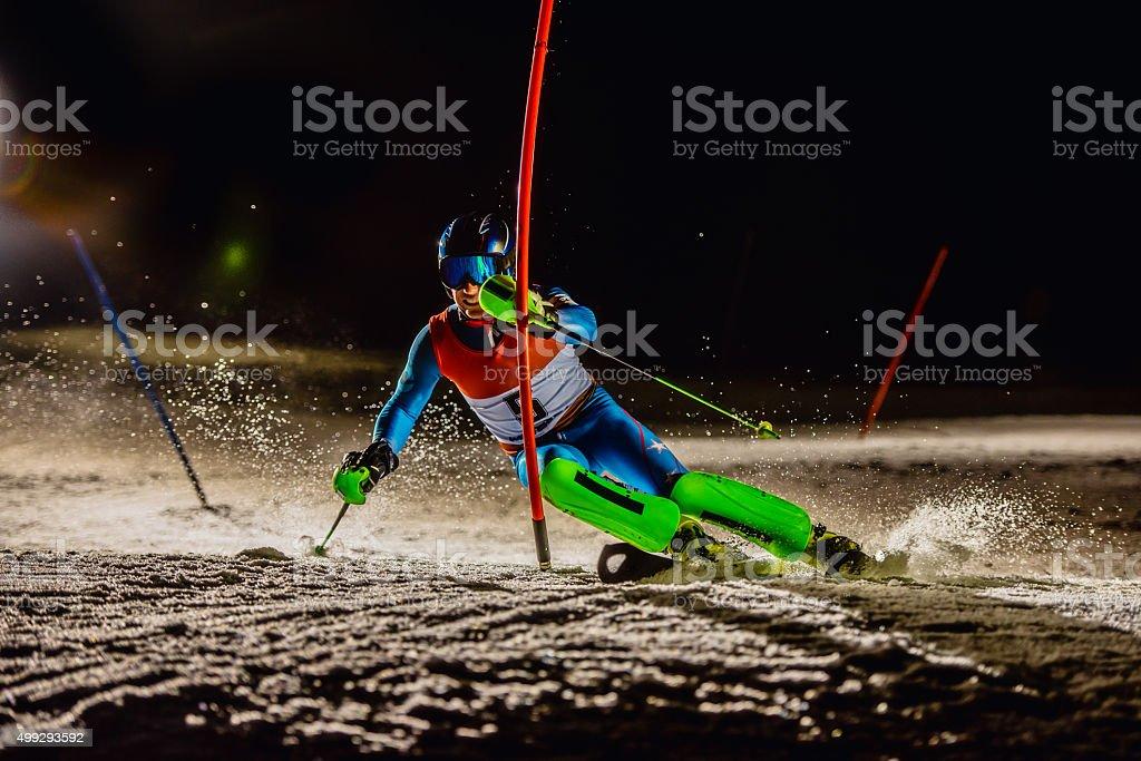 Night Shot of a Professional Alpine Skier Making Sharp Turn stock photo