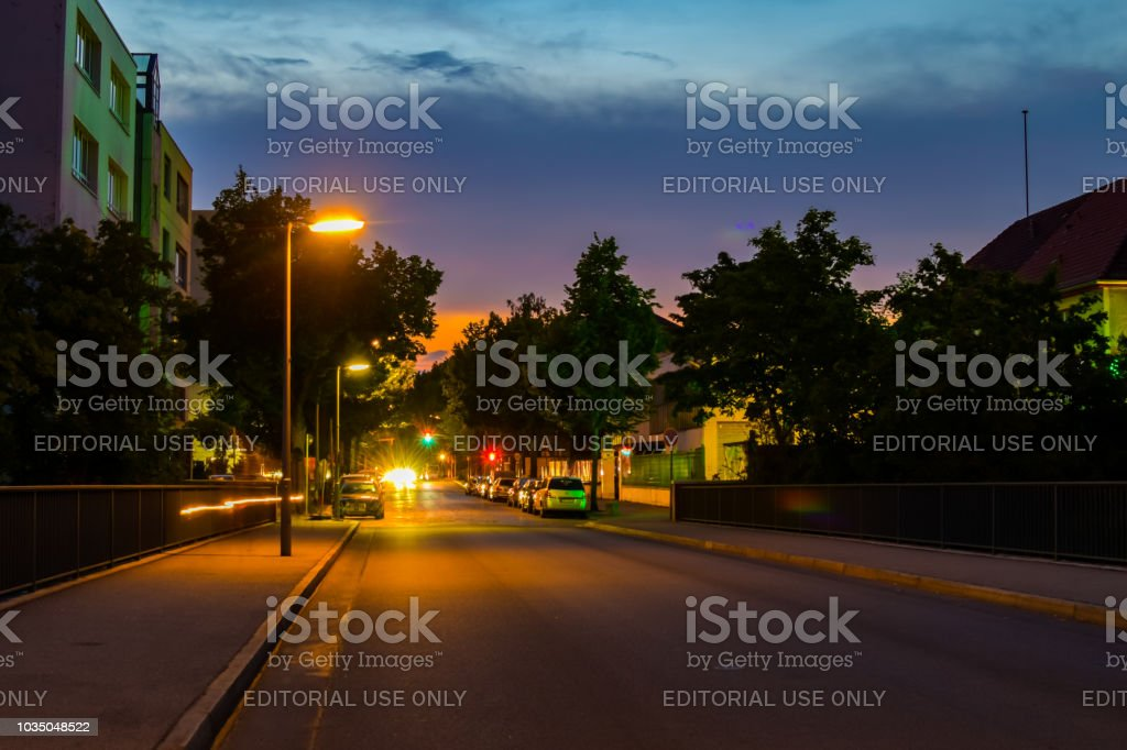 Night shot of a side street with lit lanterns, traffic lights and...