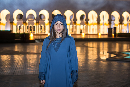 istock Night shot of beautiful young woman wearing traditional Arab clothes at Mosque Abu Dhabi, United Arab Emirates. 931197746