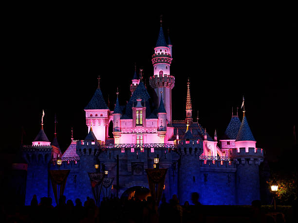 night shot of disney's sleeping beauty castle in fantasyland - castle stock photos and pictures