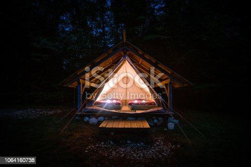 istock Night shot of illuminated tents in Adrenaline Check eco camp, Slovenia. 1064160738