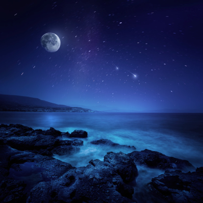 Shot of sea at night against stars and full moon.