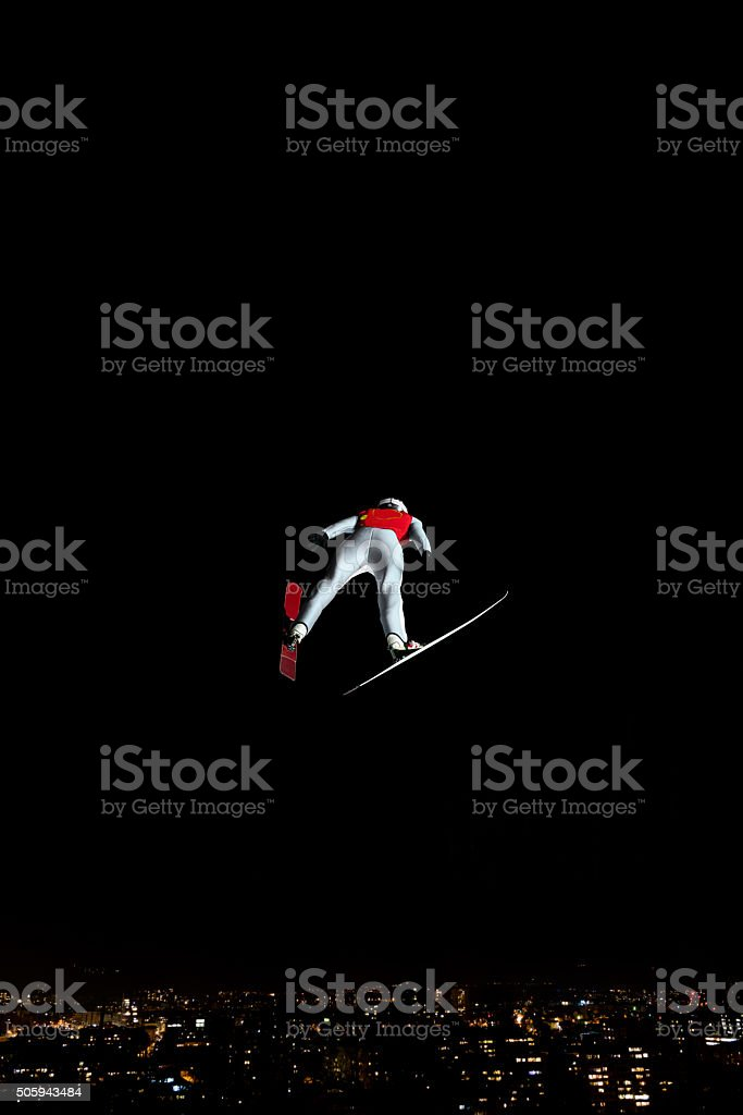 Night Shot of Ski Jumper in Mid-air, Cityscape stock photo