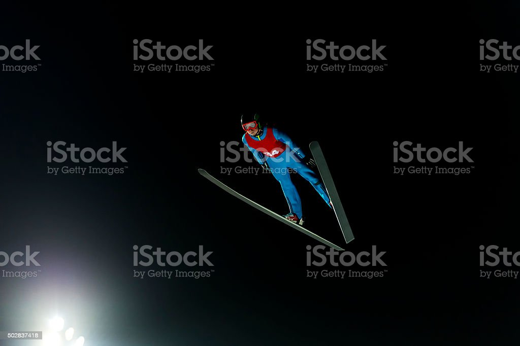 Night Shot of Ski Jumper in Mid-air stock photo