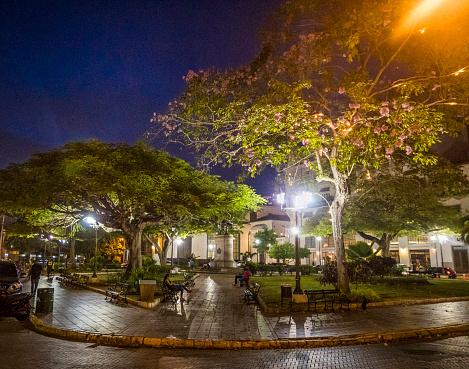 Night shot of Tomas Herrera Plaza and, behind it, buildings and a statue representing him in Casco Viejo also called Casco Antiguo Panama City's Old Quarter.