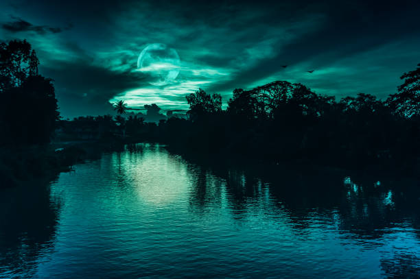 Night sky and full moon behind partial cloudy above silhouettes of trees at riverside. stock photo