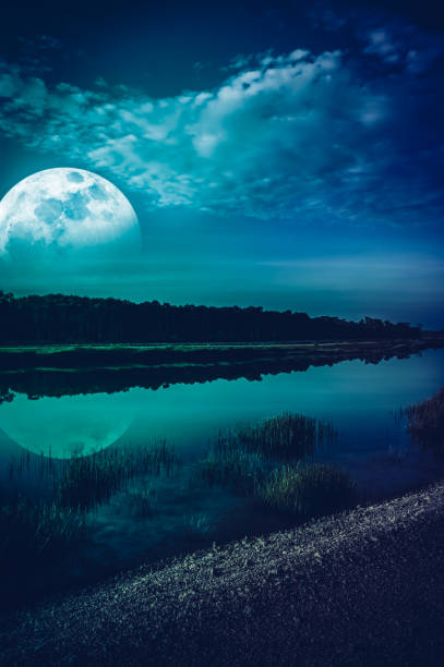 Night sky and super moon at riverside. Serenity nature background. stock photo