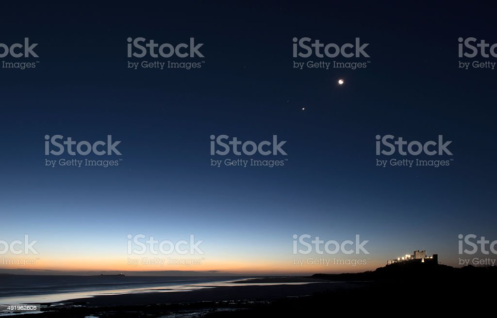 Night Sky over Northumberland Beach and Bamburgh Castle stock photo