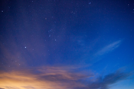 night sky with clouds and stars and constellations.  light from albuquerque colors the clouds.  horizontal wide angle composition with copy space taken in the ojito wilderness.  new mexico.