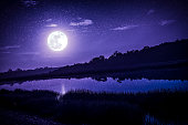 Beautiful landscape of violet sky with many stars and full moon above silhouettes of trees at riverside. Serenity nature background, outdoor at nighttime. The moon taken with my camera.