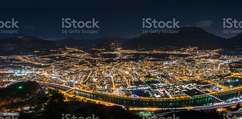 Night skyline of city in mountain valley, Trento, Italy stock photo