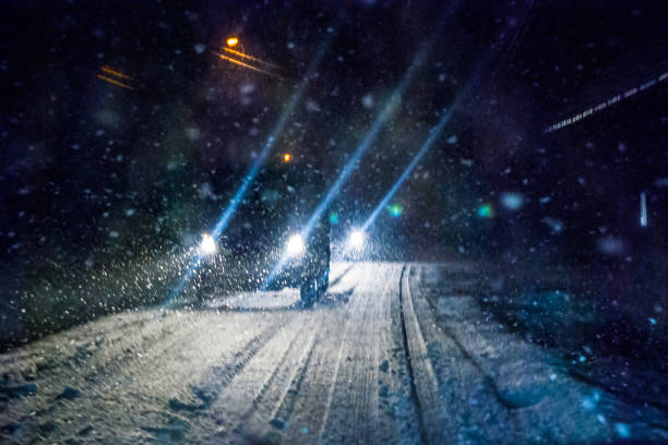 Night Snowstorm Car Lights Car driving during winter snowstorm. Motion blur. blizzard stock pictures, royalty-free photos & images