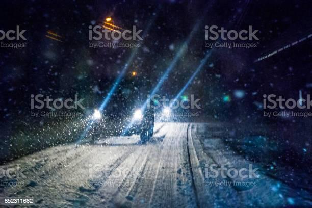 Photo of Night Snowstorm Car Lights