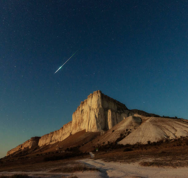 Night star sky and meteor over rock stock photo