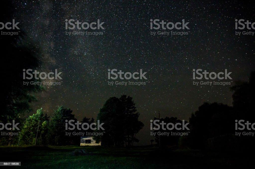 Night starry sky scene with illuminated cottage royaltyfri bildbanksbilder