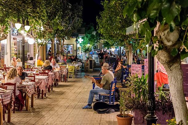 night street with tavernas full of tourists and street musicians - griechische partyspeisen stock-fotos und bilder