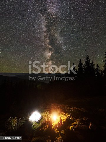678554980istockphoto Night summer camping in the mountains under night starry sky 1130760252