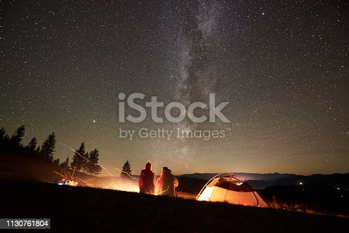 678554980istockphoto Night summer camping in the mountains under night starry sky 1130761804