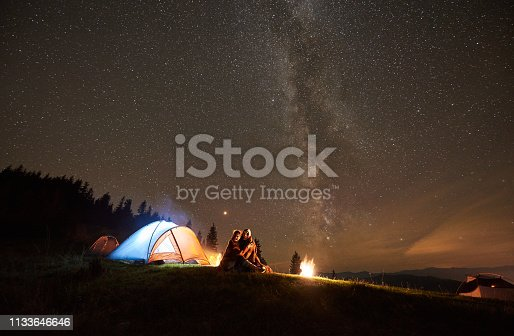 Night summer camping in the mountains. Happy couple hikers sitting together beside bonfire and glowing tourist tent. On background forest and beautiful night starry sky full of stars and Milky way.