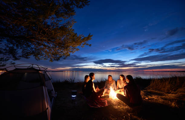 night summer camping on shore. group of young tourists around campfire near tent under evening sky - falò foto e immagini stock