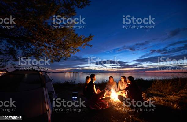 Photo of Night summer camping on shore. Group of young tourists around campfire near tent under evening sky