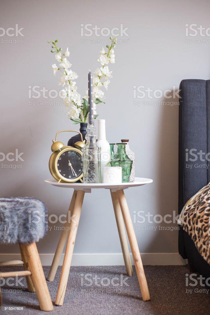 Nachttisch mit Dekoration Wecker und weißen Blüten Panther print Decke – Foto