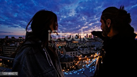 Friends talking and admiring the view. Night panorama of the city. Romantic illumination