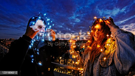 Friends talking and joking with led lights. Night panorama of the city