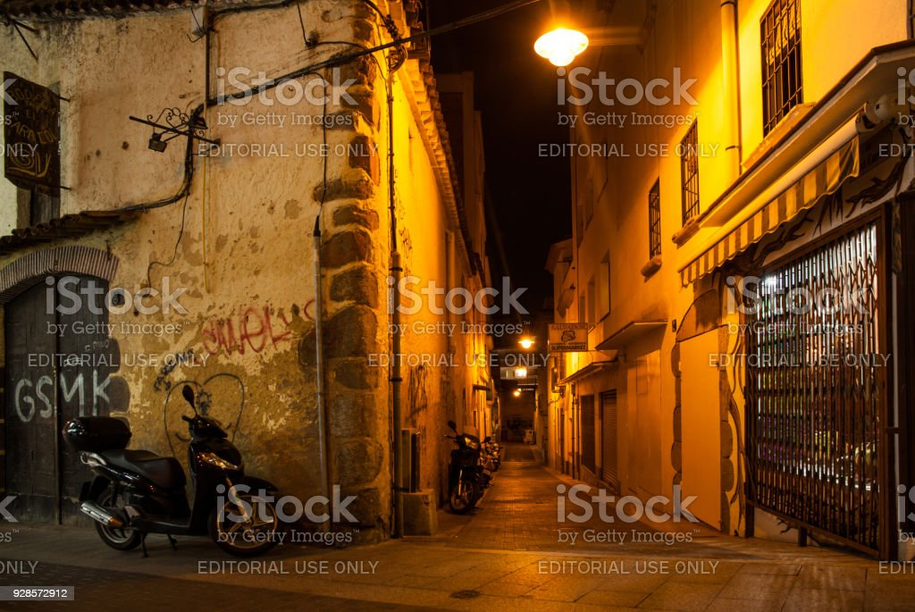 Night time homes near the narrow streets of Lloret de Mar. Downtown of Lloret, Spain. Tourists walking the streets of the city. stock photo