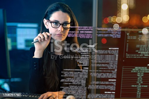 Close up stock photo of a good looking professional woman looking at data on a virtual screen She is surrounded by computer monitors & screens in a technology laden office at night.