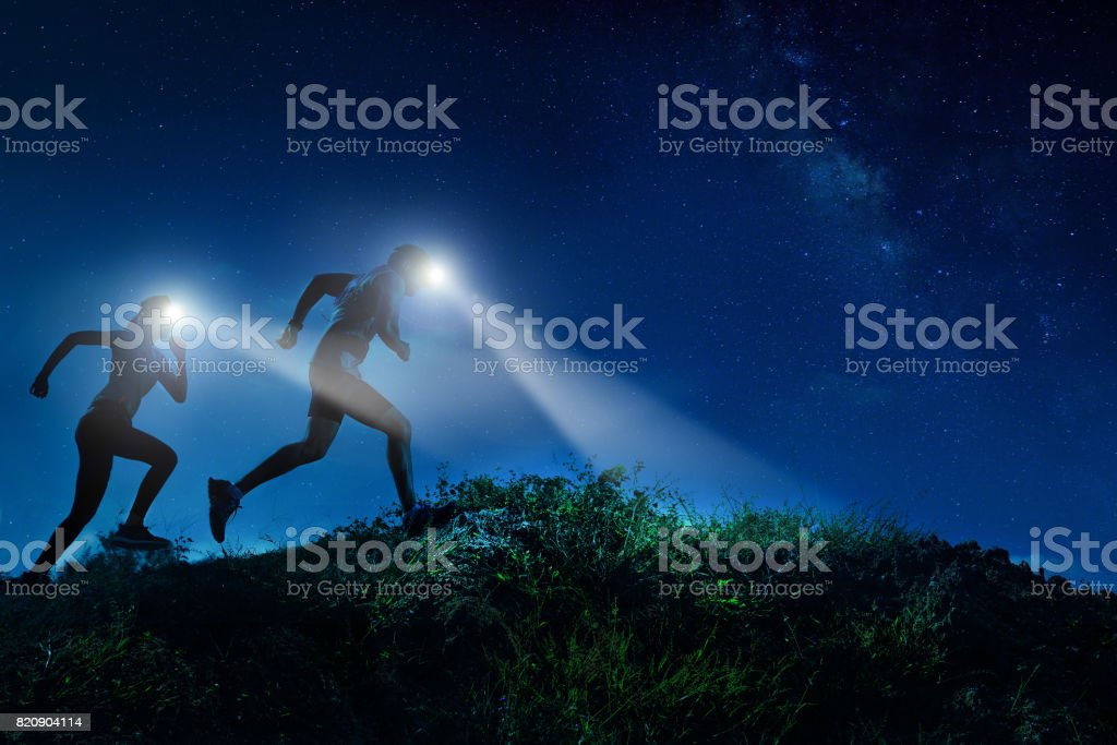 Night trail runner of men and women running on the mountain.at night milky way stock photo