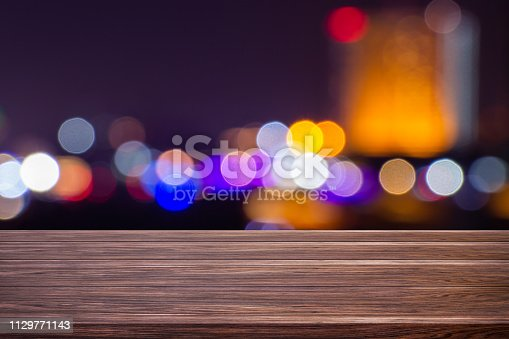 istock Night twilight blurred light bokeh in downtown bangkok empty of dark wood table abstract background for montage product display or design. 1129771143