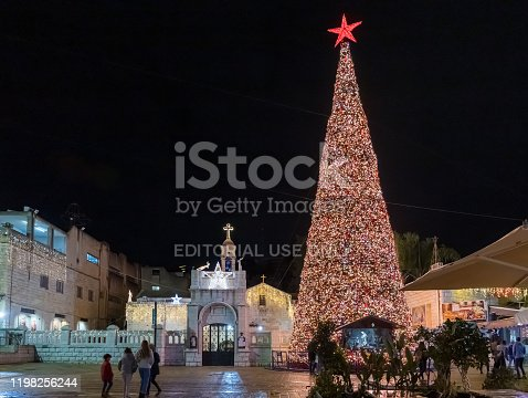 istock Night view of a Christmas tree decorated for the celebration of Christmas in the square in the old part of Nazareth in Israel 1198256244