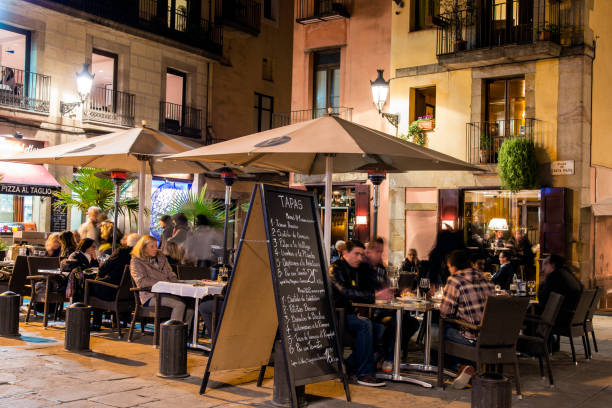 Night view of an outdoor cafe bar and people seated at tables, Santa Maria del Mar Square, Barcelona, Catalonia, Spain stock photo