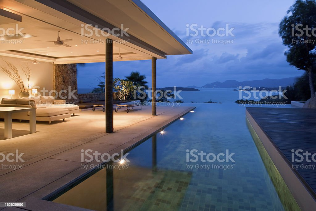 Night view of beautiful villa on island Luxury Island Villa With Infinity Pool At Sunset. Architecture Stock Photo