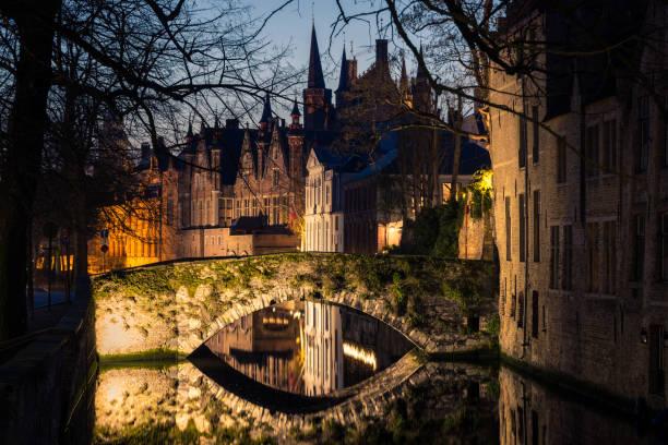 Nachtansicht von Brügge mit traditionellem Kanal, Steinbrücke, Bäumen und Architektur, Belgien. – Foto