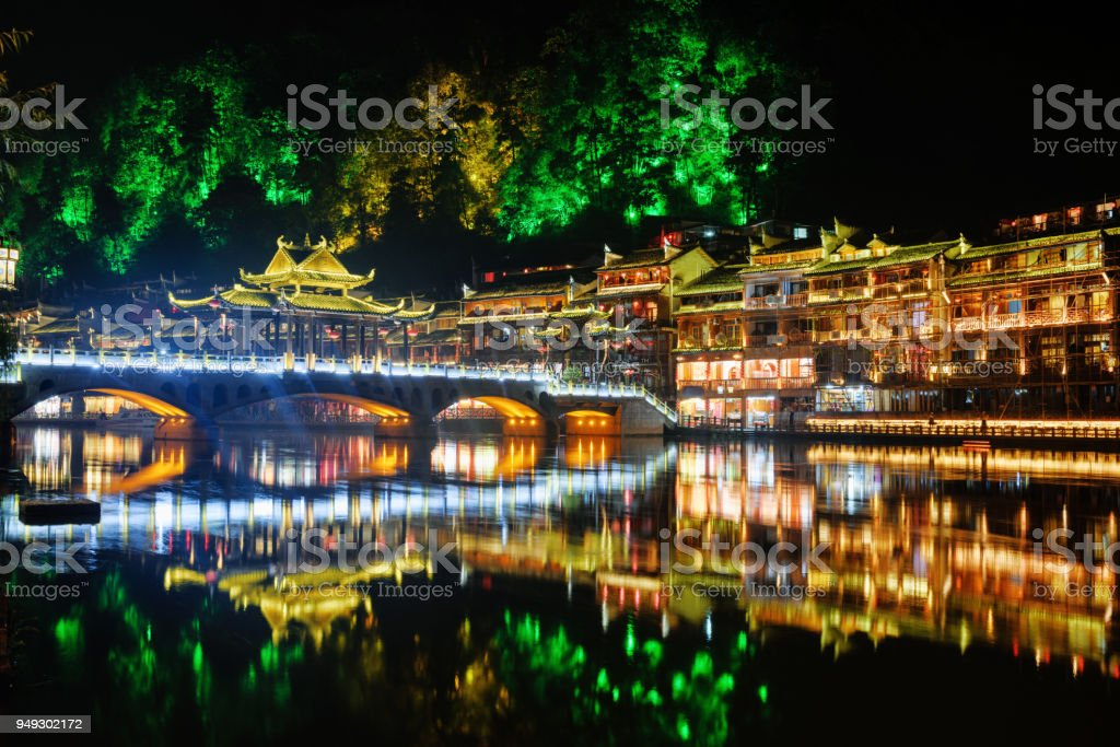 Night view of colorful bridge and traditional Chinese buildings stock photo