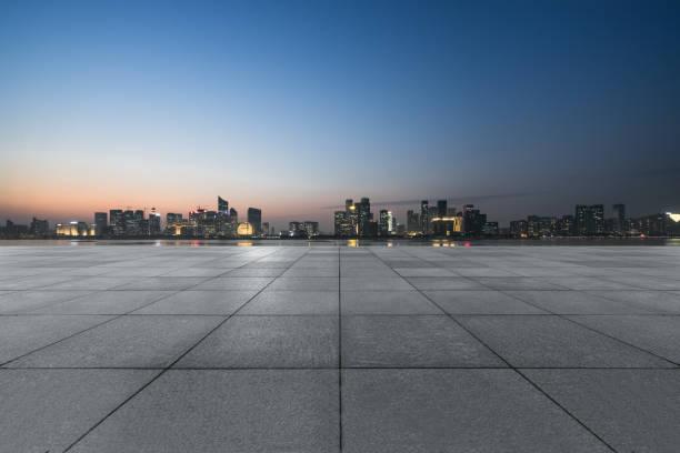 vista nocturna del piso de ladrillo vacío frente al edificio moderno - ciudad fotografías e imágenes de stock