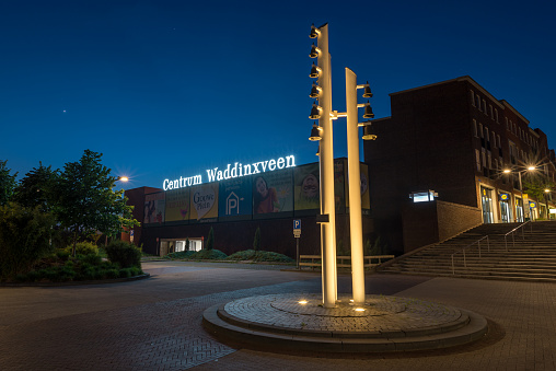Waddinxveen, Netherlands - May 2020: Entrance of modern centre of the town of Waddinxveen, Holland at night. Traditional chimes or carillon in the foreground.