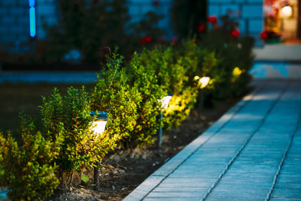 Night View Of Flowerbed With Flowers Illuminated By Energy-Saving Solar Powered Lanterns Along Path Causeway On Courtyard Going To The House stock photo