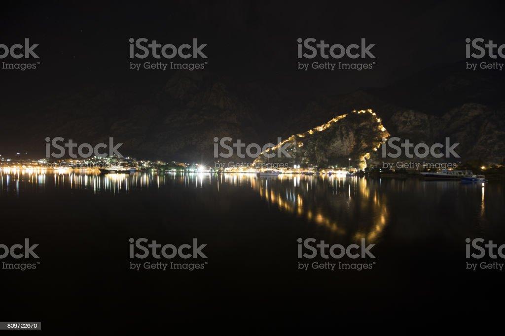 Night view of Kotor Fortress wall up to Lovcen Mountain with heart-shape reflection in water. Montenegro, Kotor Bay (Boka Kotorska stock photo