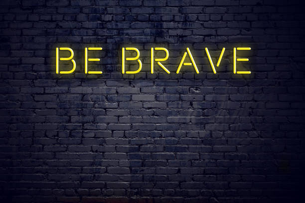 Night view of neon sign with text be brave stock photo