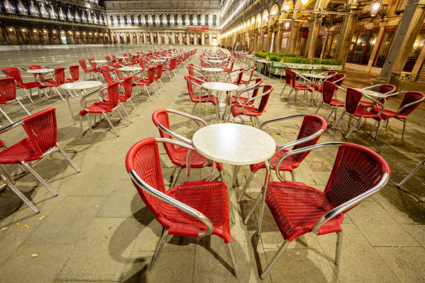 Night view of one Bar on the Piazza San Marco showing a multitude of empty chairs and empty square stock photo