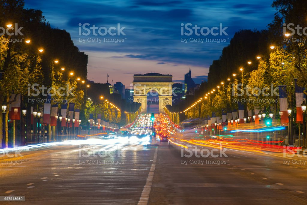 Night view of Paris traffic in Champs-Elysees street and the Arc de Triomphe in Paris, France. stock photo