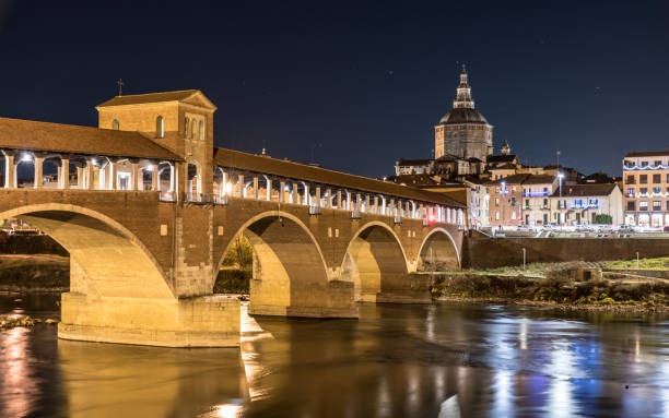 Night view of Pavia with Ponte Coperto and the river Ticino stock photo
